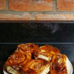 sticky buns on a plate against a red brick wall