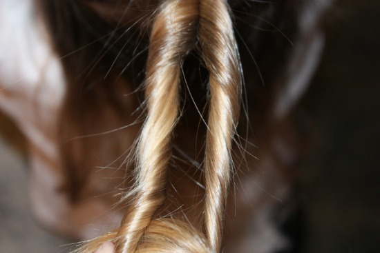 Twisting the strand of hair for a heart hairstyle