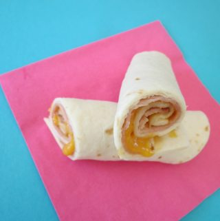 Looking for a simple back to school lunch idea that can be made in no time. Ham and Cheese Roll Ups are perfect for a quick lunch idea.