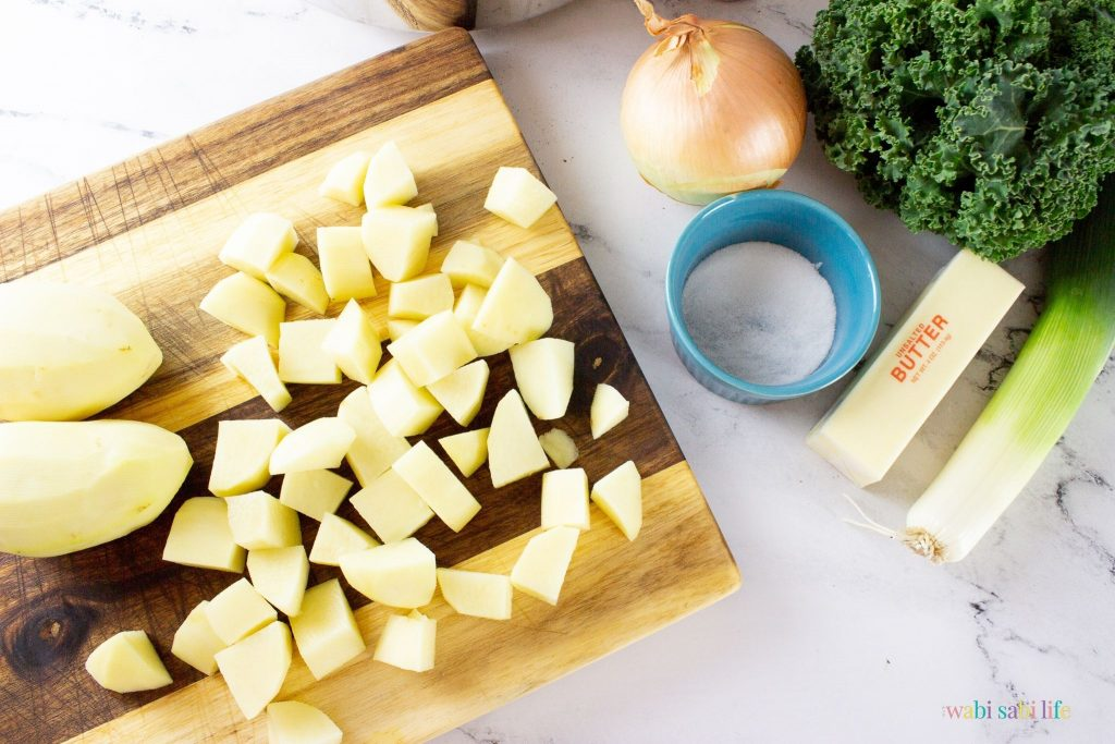 Peeled and cut up potatoes on a wooden cutting board