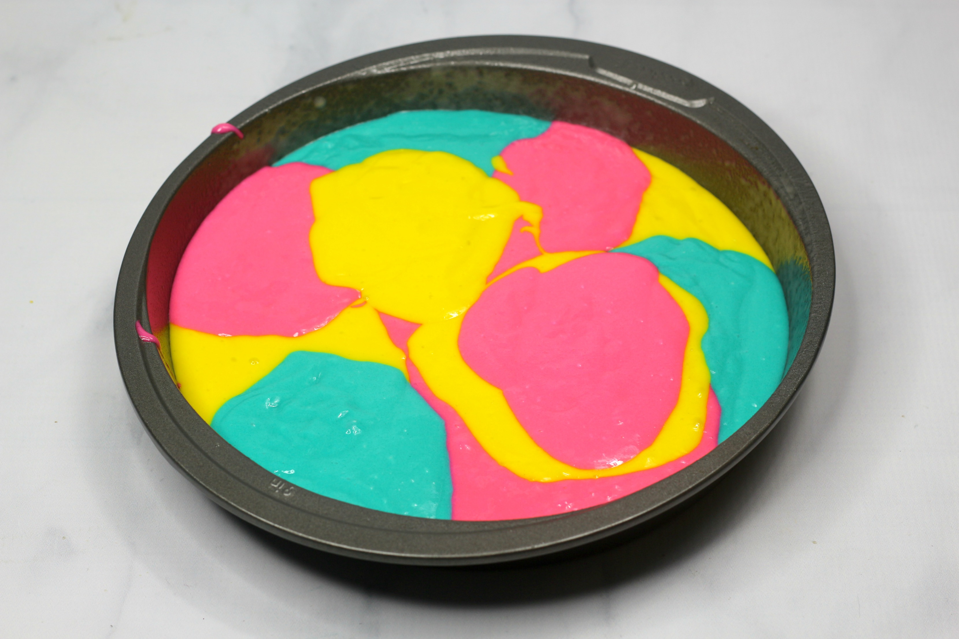 tie dy cake batter in a cake pan