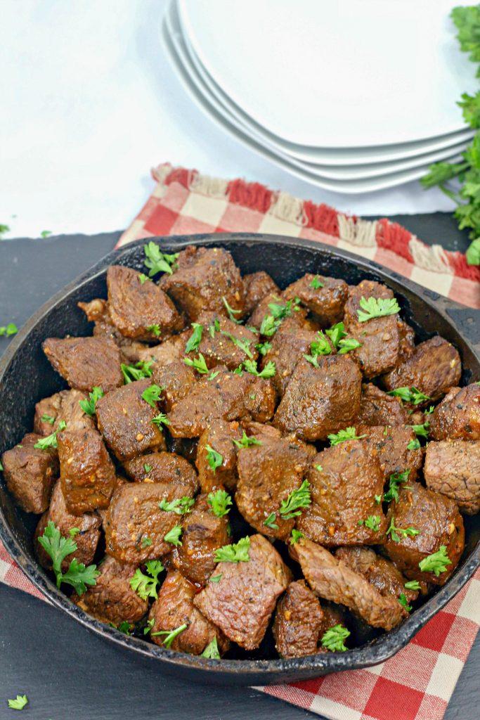 cajun garlic butter steak in a cast in a pan