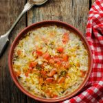 turkey and rice soup on a wood background with a checkered napkin