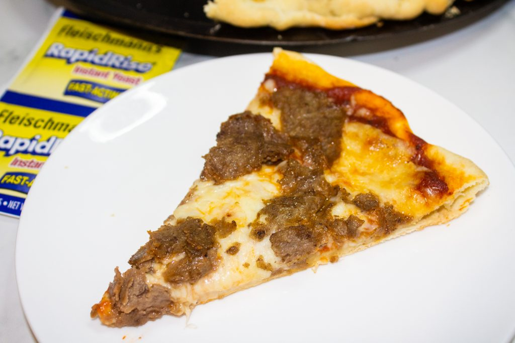 slice of cheesesteak pizza on a white plate