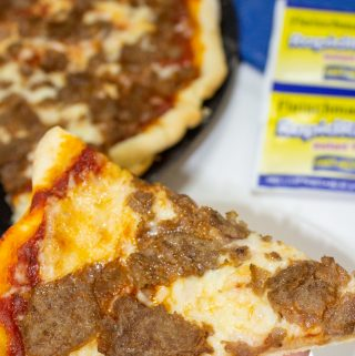 slice of cheesesteak pizza in hand