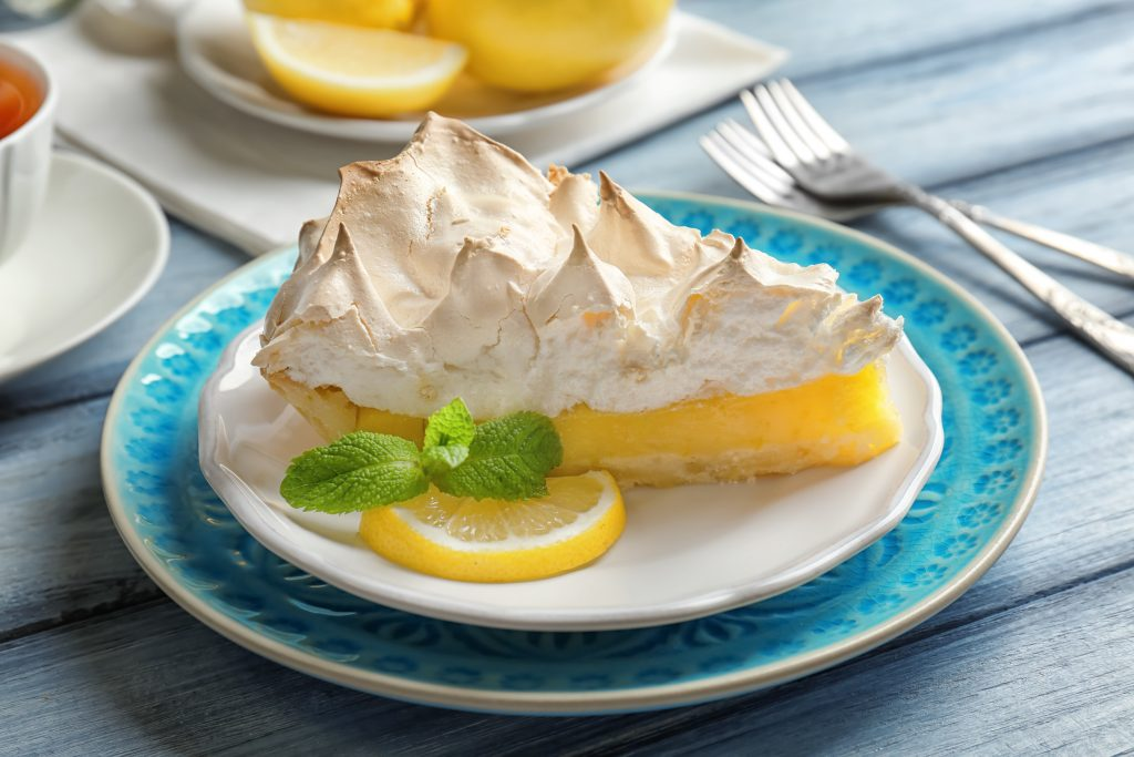 lemon merinque pie on a white and blue plate