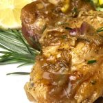 Lemon Rosemary Chicken on a white plate with rosemary and lemon