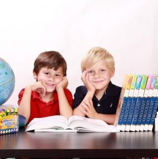 2 boys with books and globe