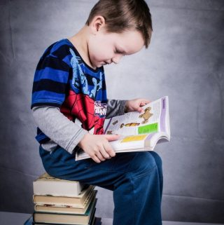 boy sitting on books reading