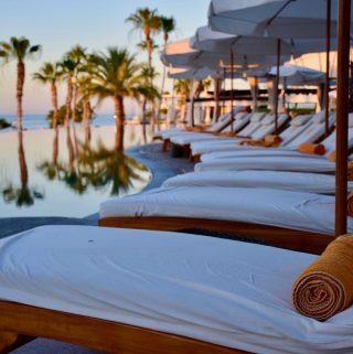 beautiful beach scene with palm trees and beach chairs