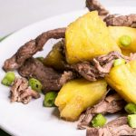 Pineapple Beef Stir Fry on a white and green plate