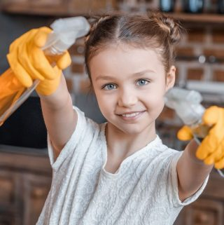 young girl holding spray bottles