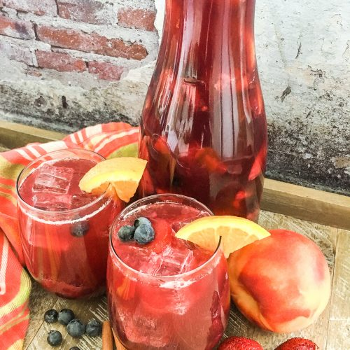 Sparkling Berry Peach Sangria in a pitcher and glasses with fresh fruit
