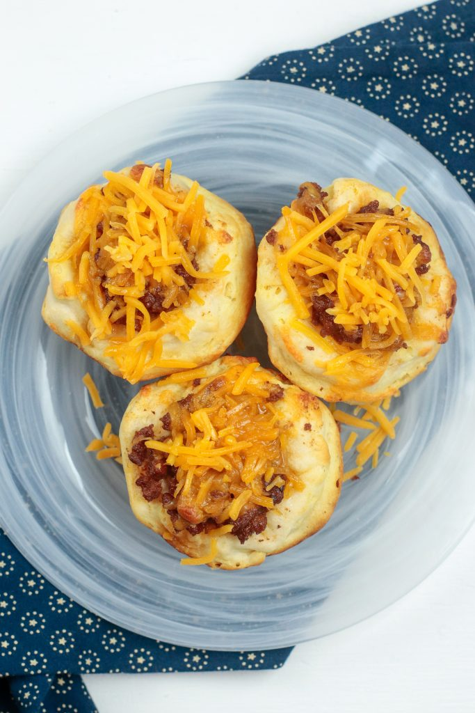 up close of cheeseburger muffin cups on a glass tray