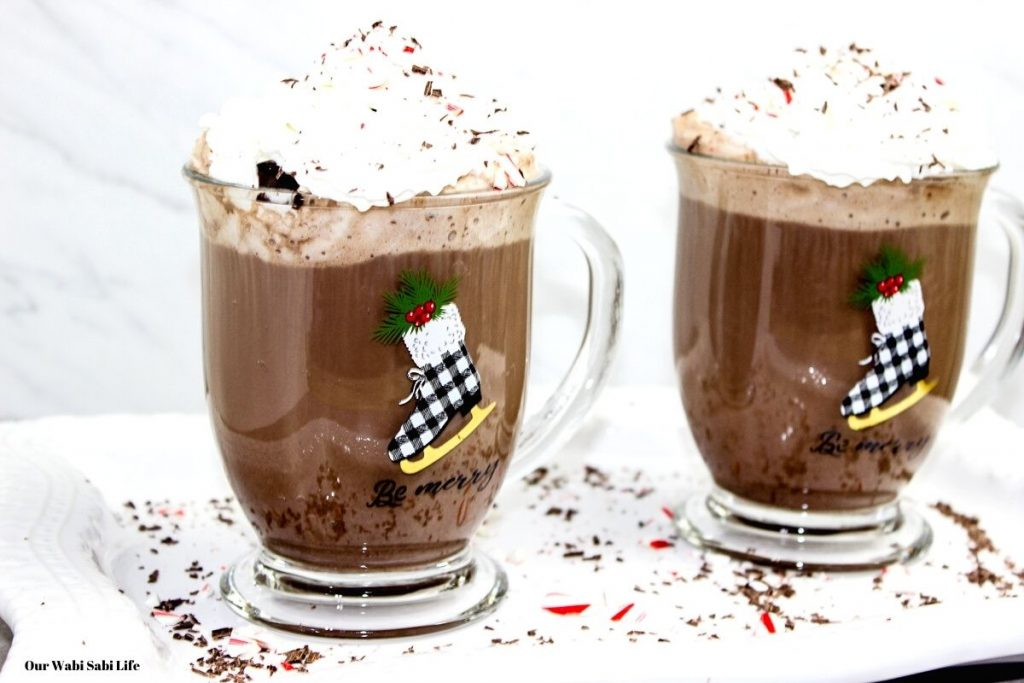 Peppermint Hot Chocolate served in two glasses topped with whip cream, peppermint, and chocolate.