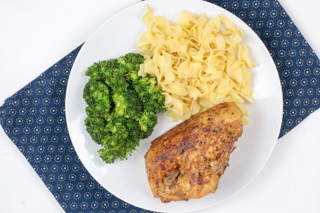 chicken breast on a white plate with broccoli and noodles