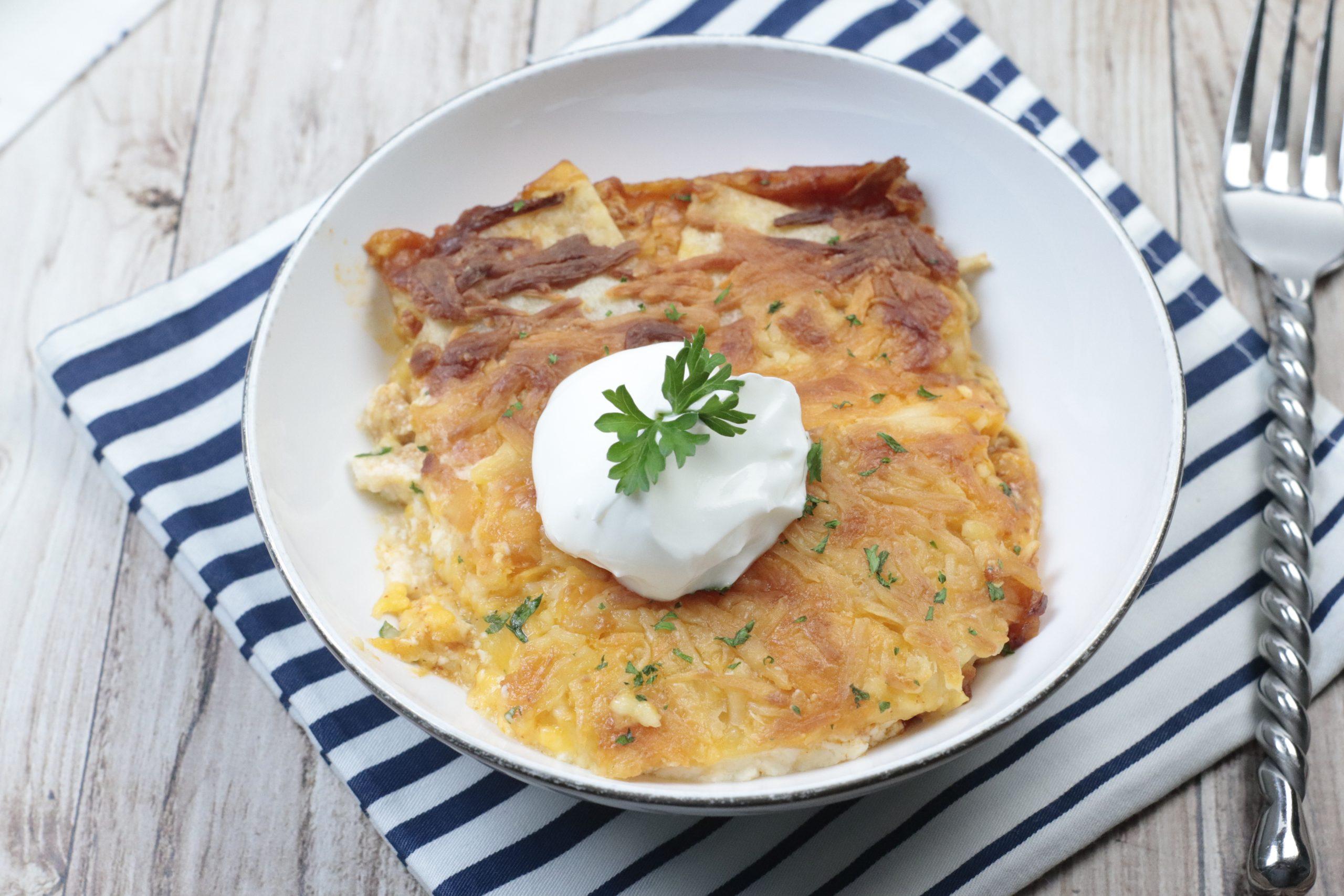 Rotisserie Chicken Enchilada Casserole in a white bowl with a dollop of sour cream