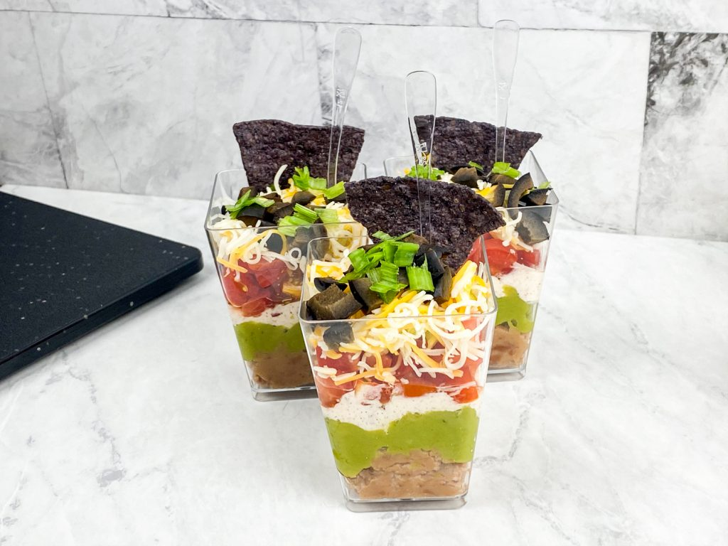 7 layer dip cups together on a white tray