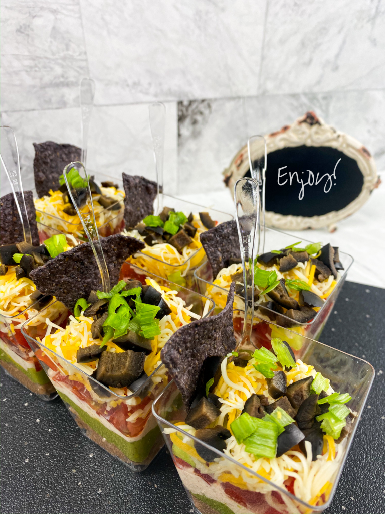 7 layer dip cups together on a gray tray