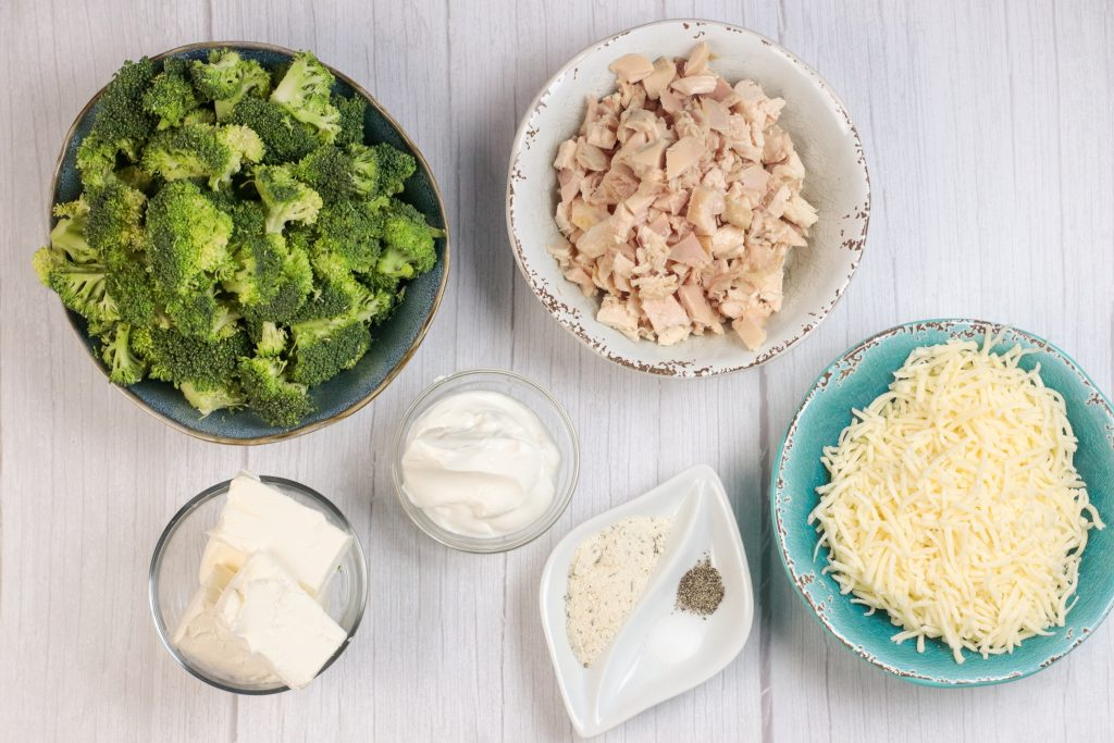 ingredients for broccoli, chicken and cheese casserole in bowls, broccoli, chicken, sour cream, cream cheese, salt, pepper, ranch seasoning and cheese