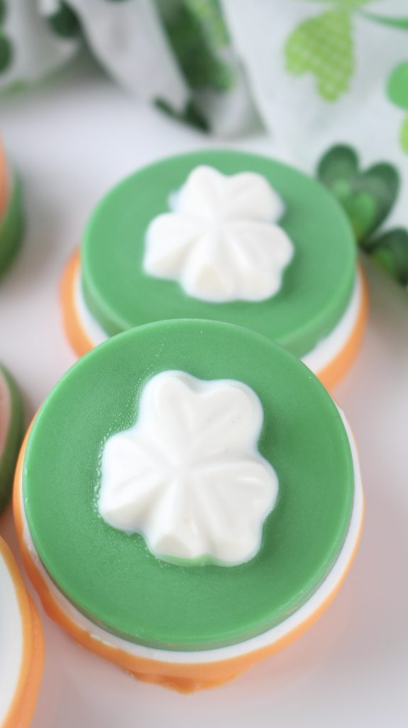 green cookie with a. white shamrock on top