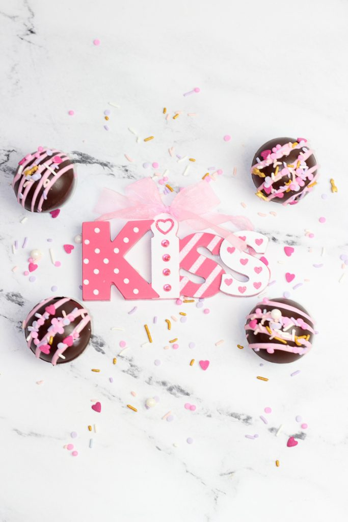Hot Cocoa Bombs for Valentines Day surrounded by sprinkles
