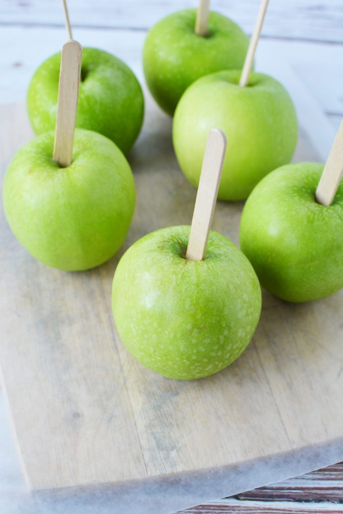 Sticking stick into the top of the green apples
