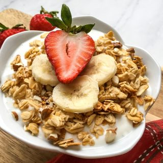 Homemade Greek Yogurt in a white bowl topped with granola, bananas and a strawberry