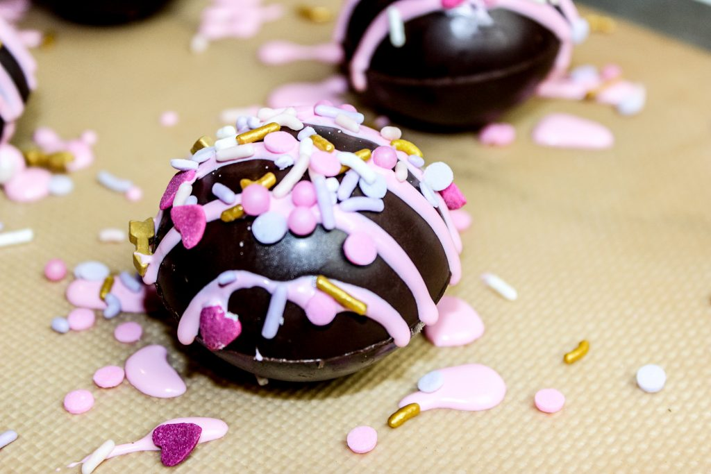 Valentines Day Hot Cocoa Bombs with pink frosting and sprinkles