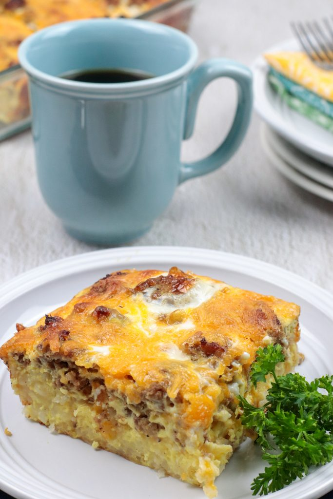 Breakfast Sausage and Egg Hash Brown Casserole on a white plate with a blue mug with coffee