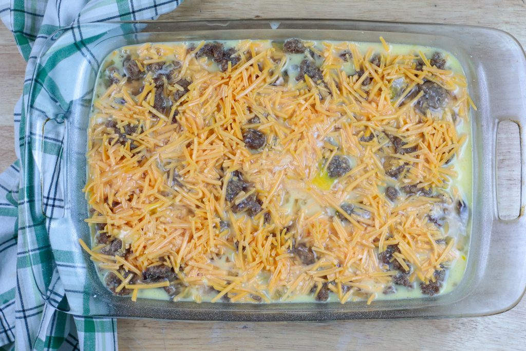 Eggs and cheese on top of cooked sausage and browned hash browns in a baking dish