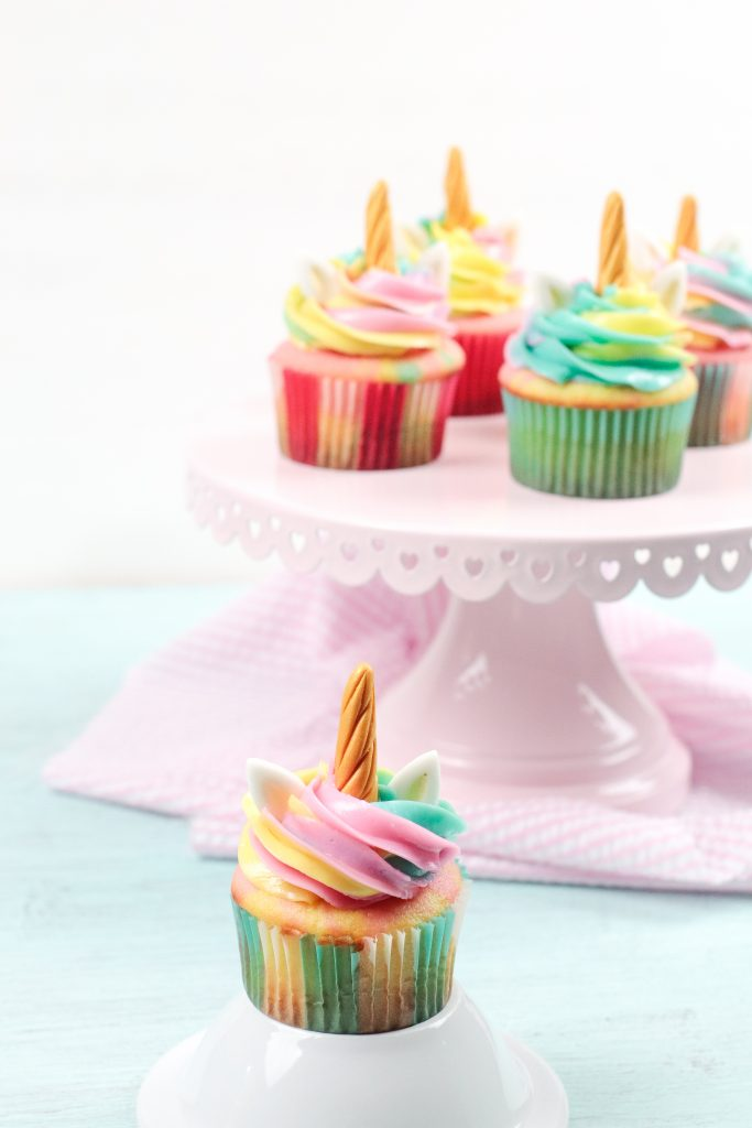 one unicorn cupcake unclose more in the background on a table
