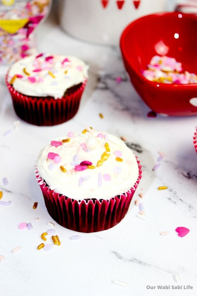 Vanilla frosted cupcakes with Valentines sprinkles in red cupcake liners