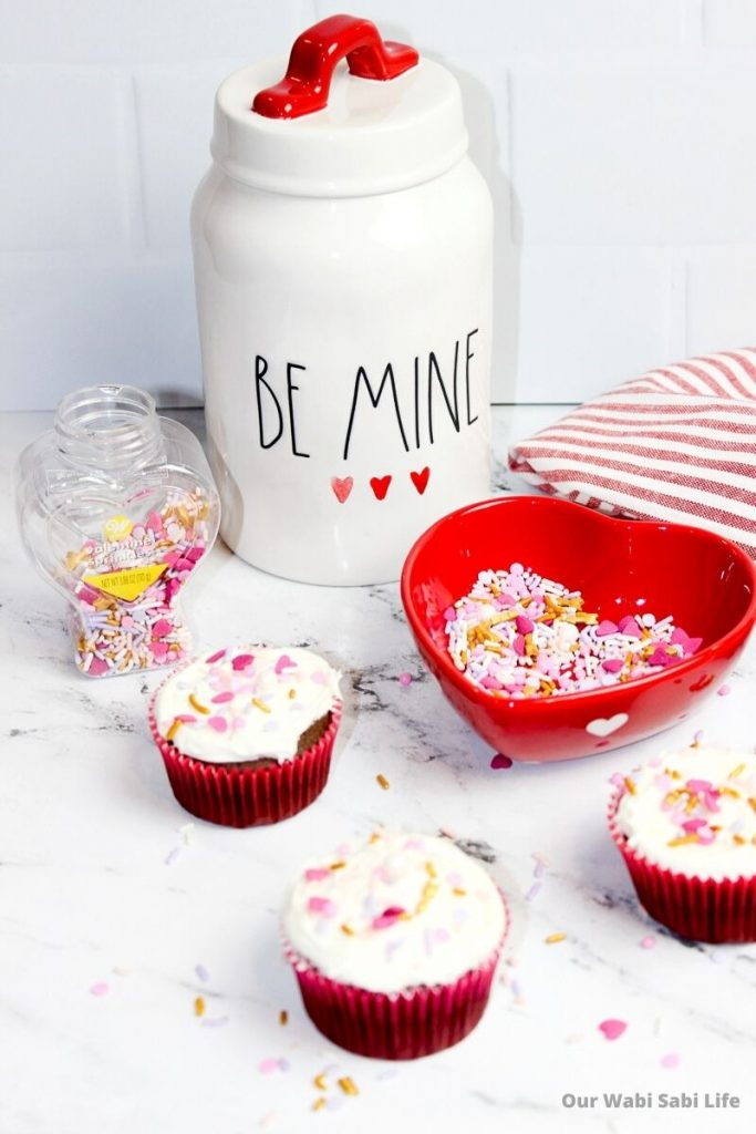 Valentine Sprinkle Cupcakes on a marble counter with a Be Mine Cookie Jar