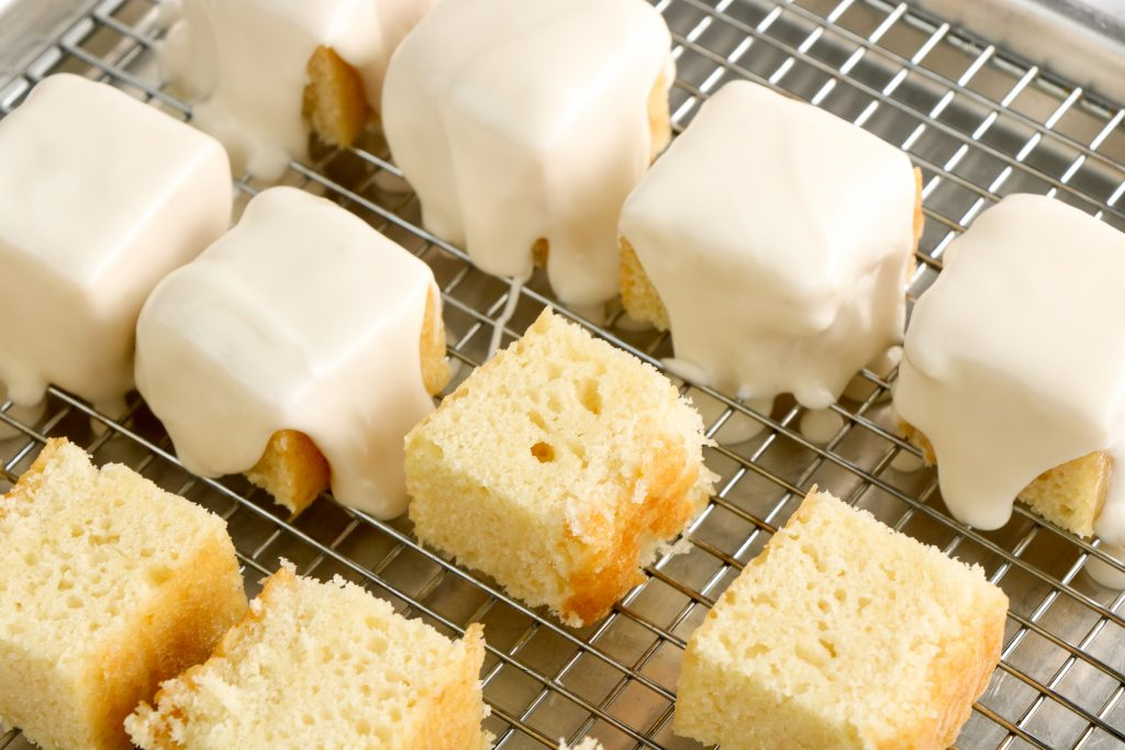 Cake squares with frosting being poured over the squares