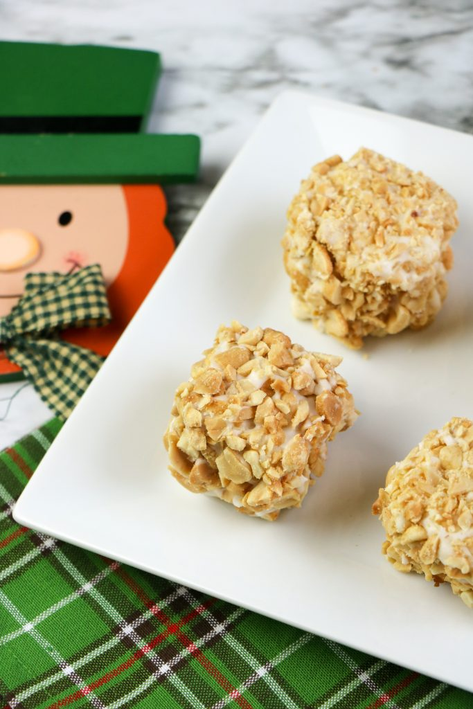 Blarney Stone Squares covered in peanuts and vanilla glaze on a white plate