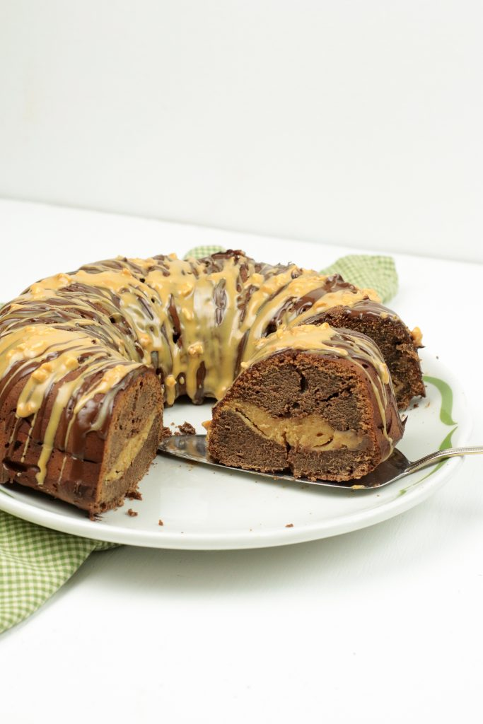 Chocolate Peanut Butter Bundt Cake full of peanut butter fluff and drizzled with chocolate and peanut butter on a white plate.