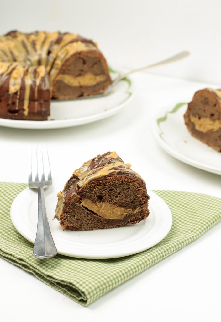A decadent slice of Chocolate Bundt Cake with a peanut butter middle and drizzled with chocolate and peanut butter
