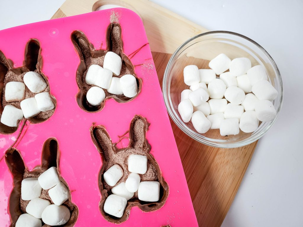 A pink mold full of melted chocolate, mini marshmallows, and hot cocoa mix