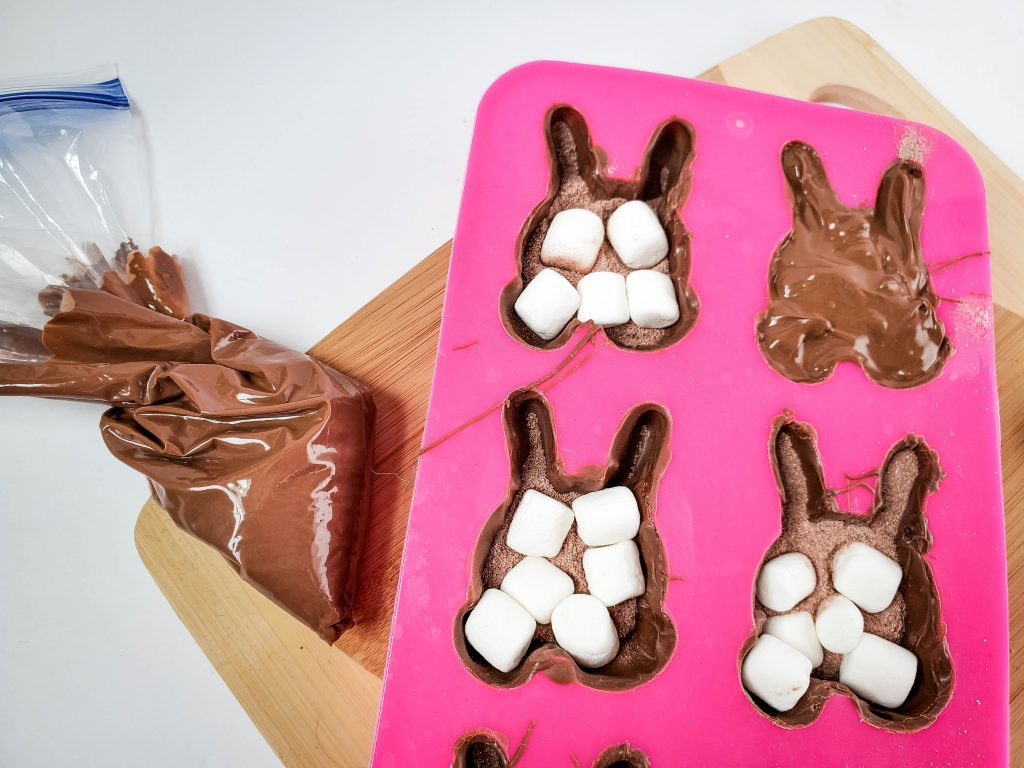 A pink mold full of mini marshmallows, hot cocoa mix and covered with melted chocolate