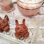 Two bunny faces made out of chocolate next to a glass mug of hot chocolate on a glass tray