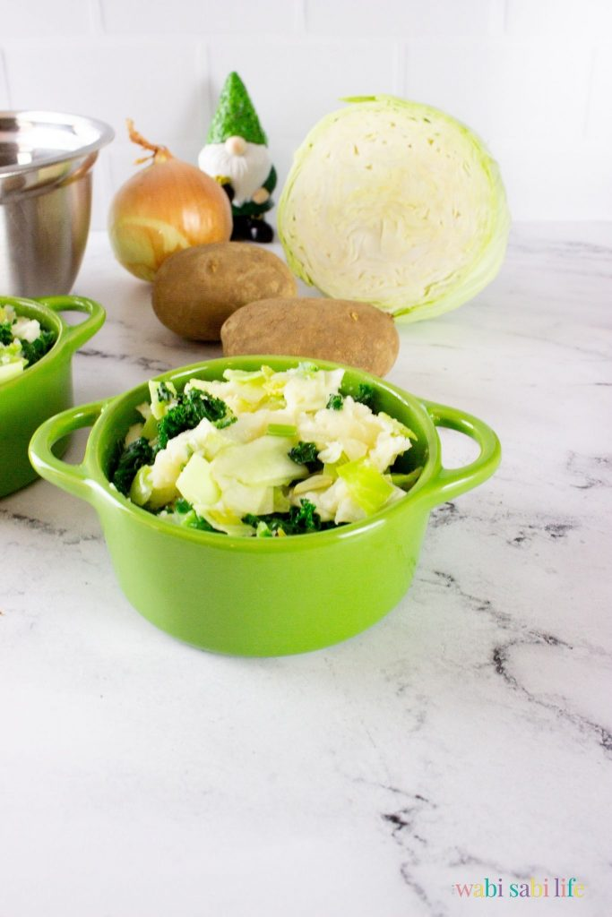 A green pot of Irish Colcannon potatoes with kale, leeks, and cabbage