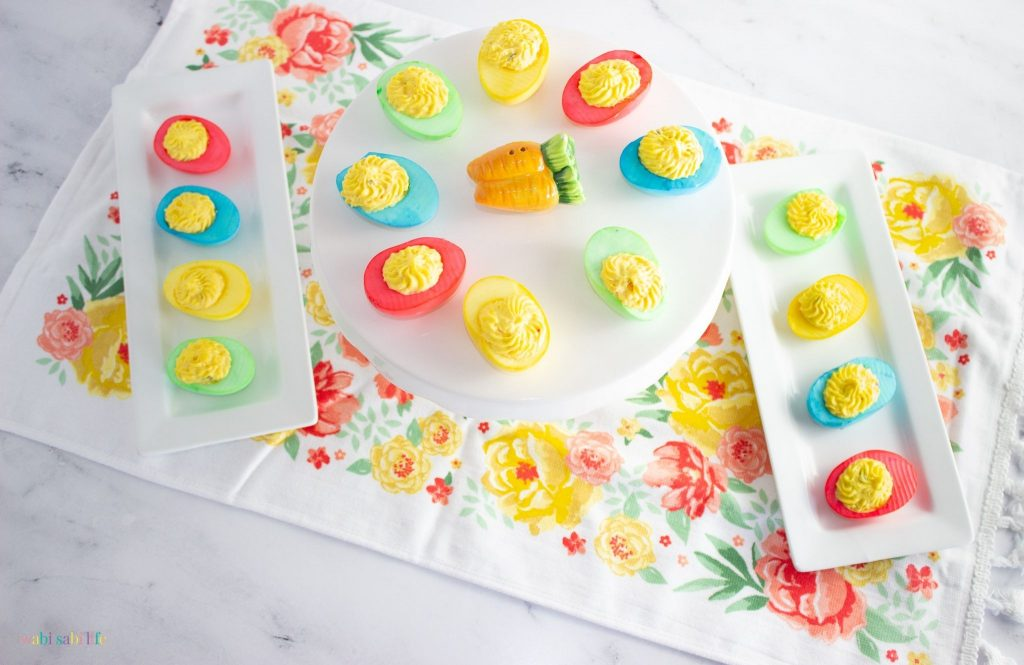 Two trays and a cake stand full of brightly colored deviled eggs