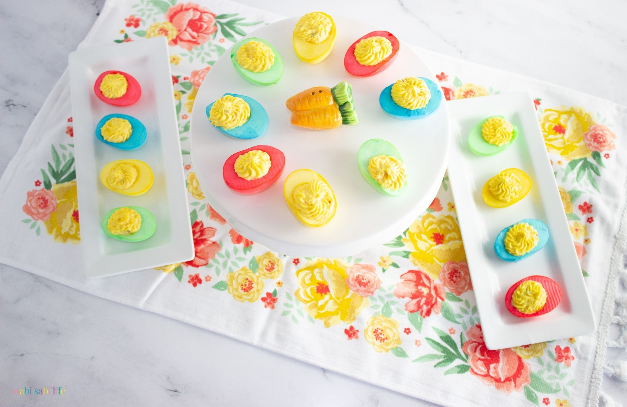 Two White trays and a cake stand full of brightly colored deviled eggs