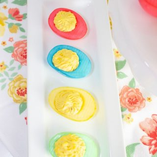Brightly colored deviled eggs for Easter on a white tray