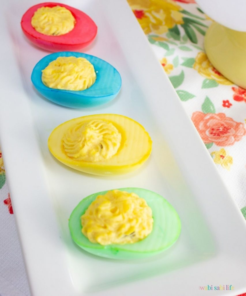colorful dyed deviled eggs lines d on a white plate