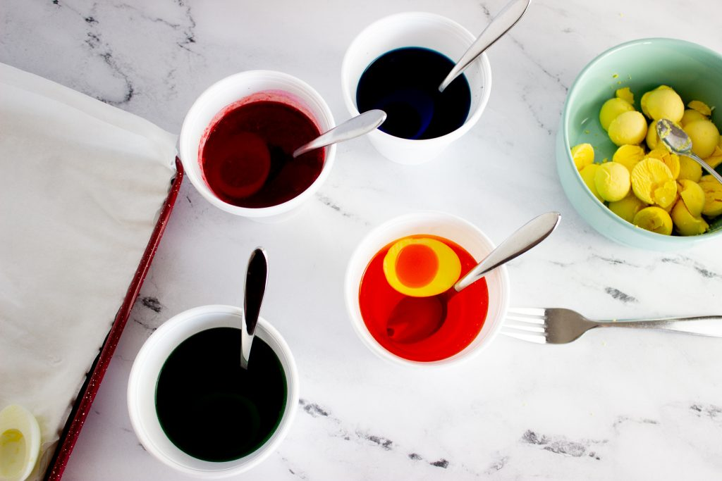 Adding eggs into colored water to color them