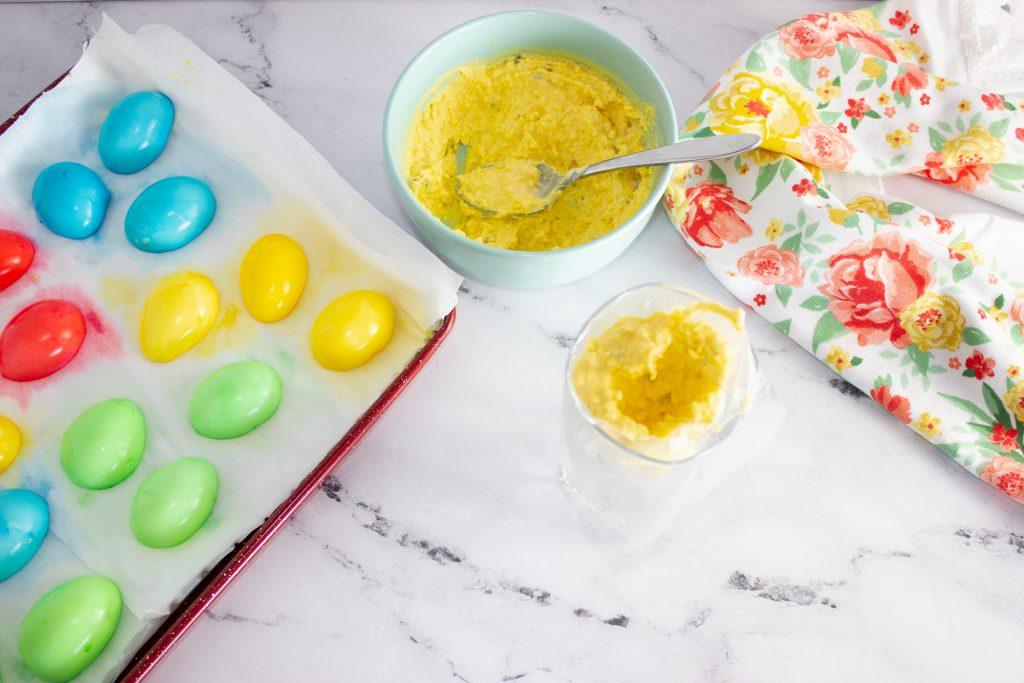 Adding egg filing into a piping bag that is in a large glass