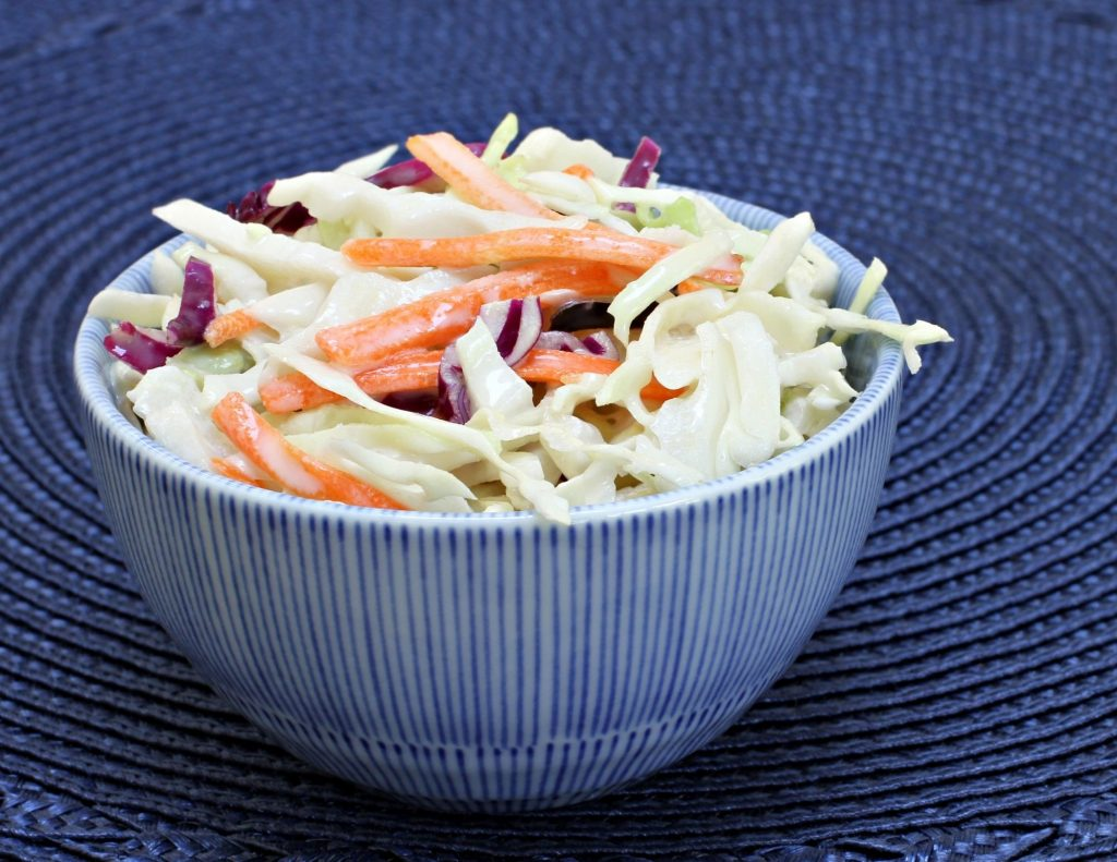 coleslaw in a blue bowl with a blue background