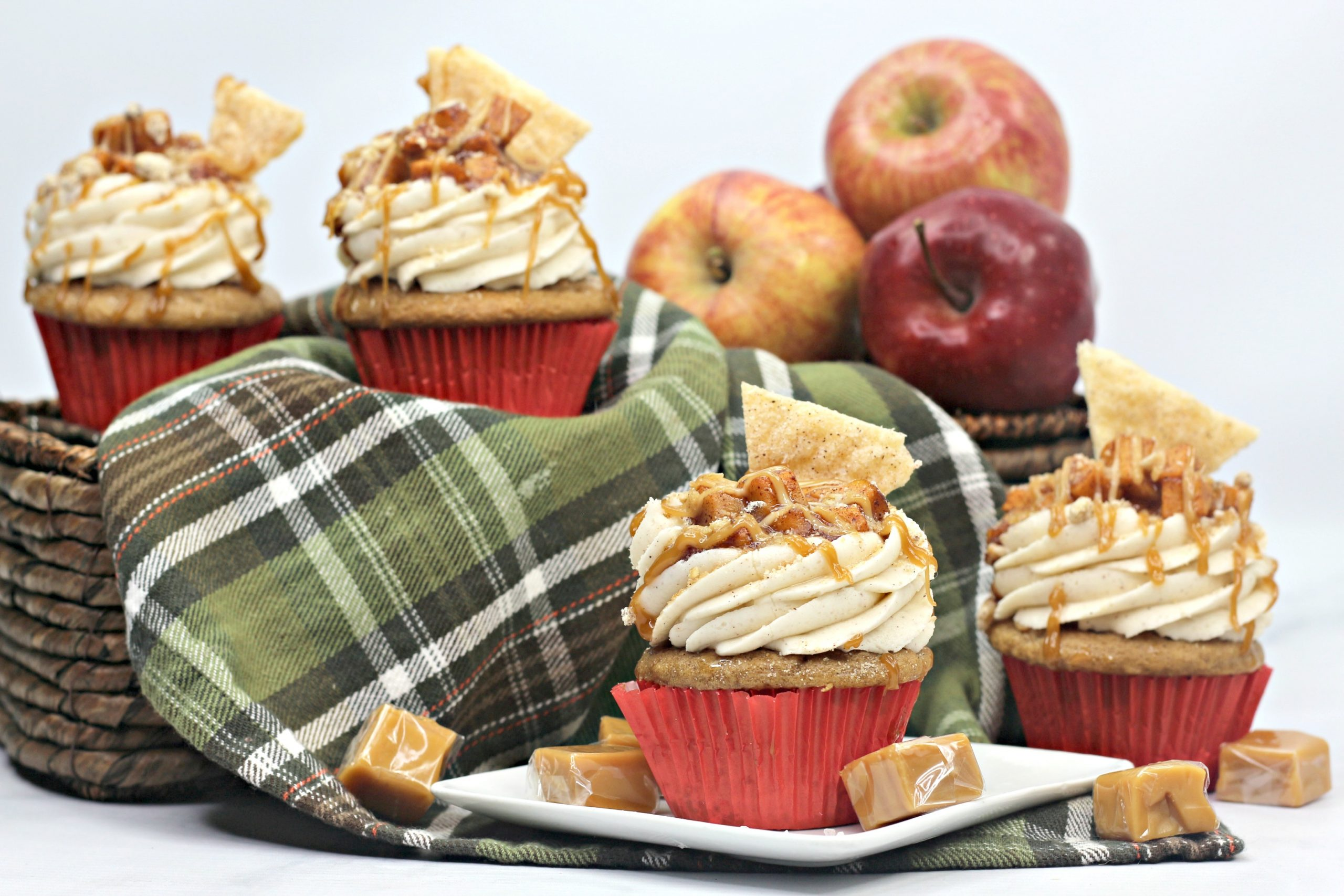 Apple Pie Cupcakes with two more behind them in a basket with more apples.